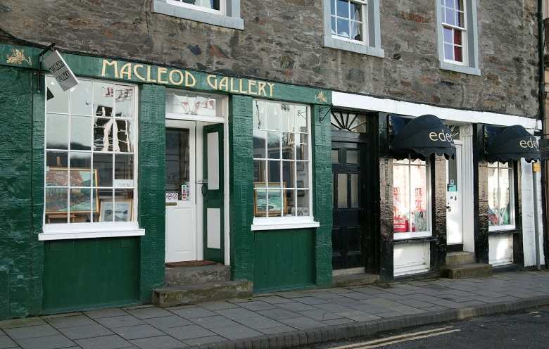 A traditional green shopfront as part of a stone building