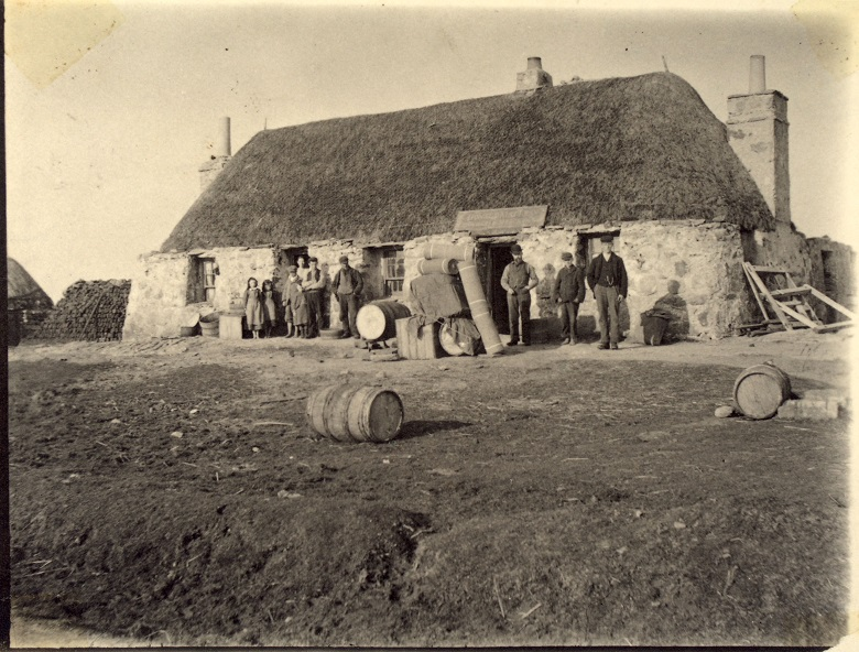 A group of people standing outside a standalone thatched building in the countryside