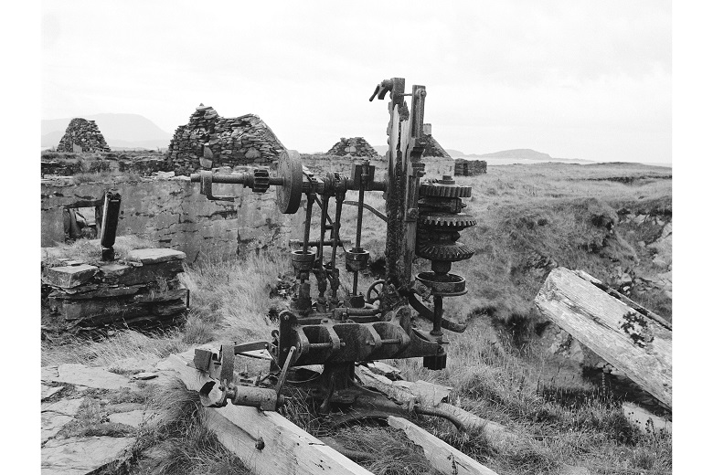 A large, rusty part of a machine lying on a grass field