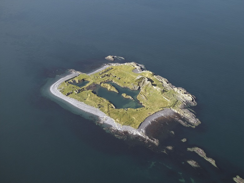 An aerial photo of a small island with few buildings visible