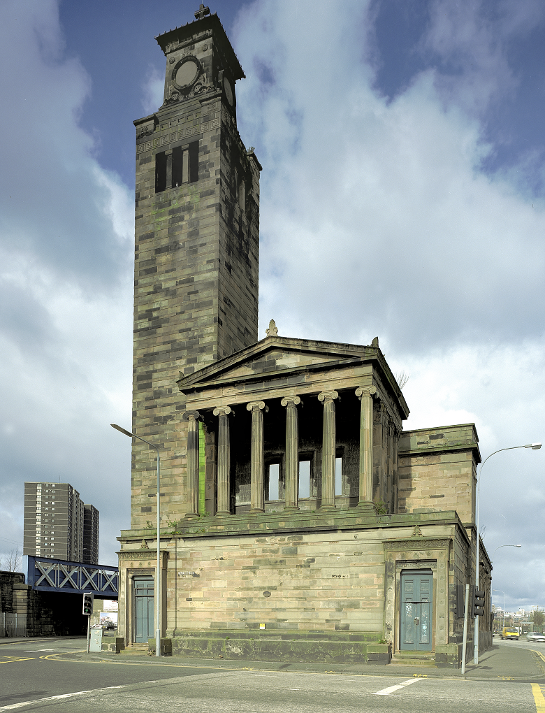 A large, stone church on a stone plinth, featuring columns