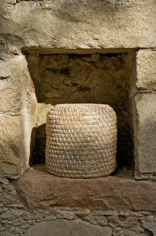 A straw basket set inside a cove in a stone wall.
