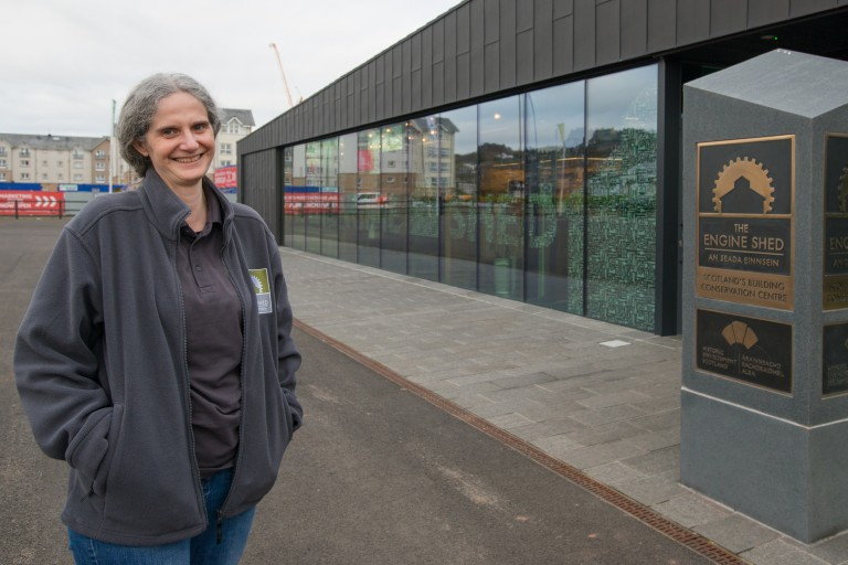 A person wearing a grey Engine Shed jumper, standing outside the building