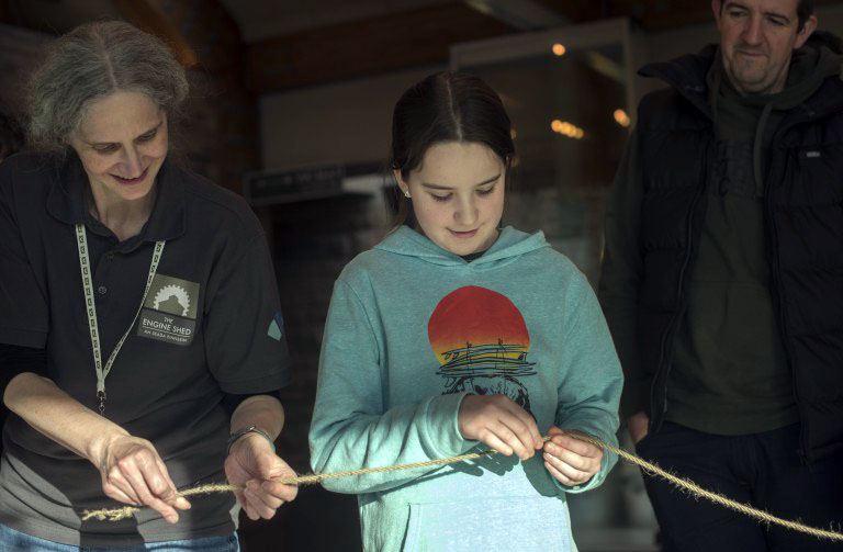 A person wearing a grey Engine Shed t-shirt, twisting a piece of rope with a young teenage child.
