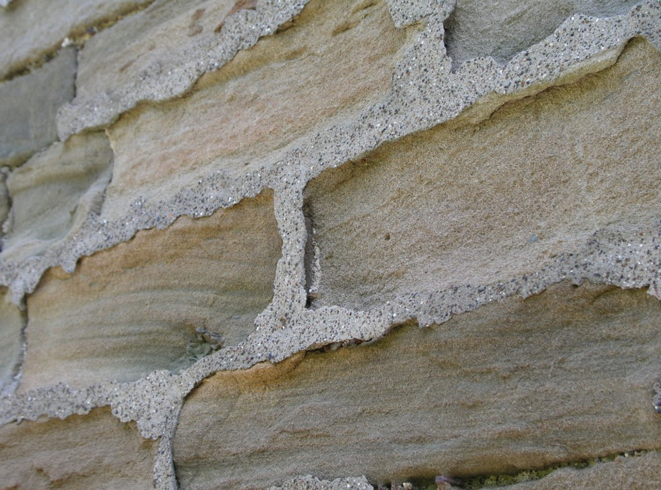 A sandstone wall with some type of cement plugging the gaps