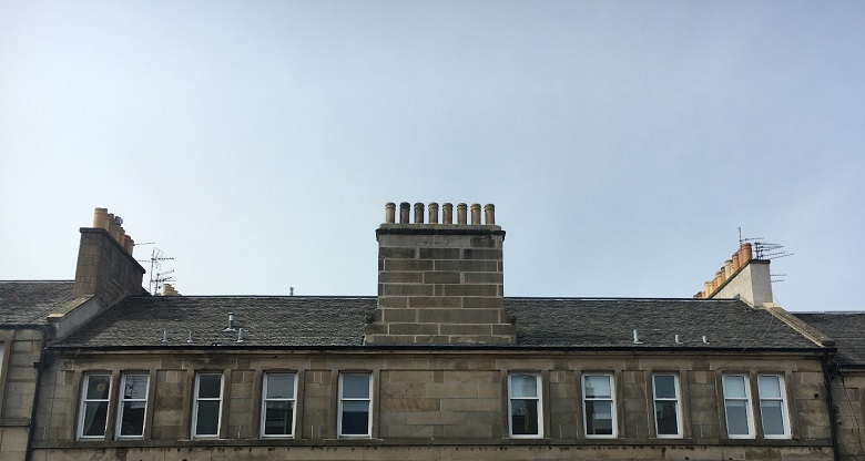 The slate roof of a tenement with multiple chimneys