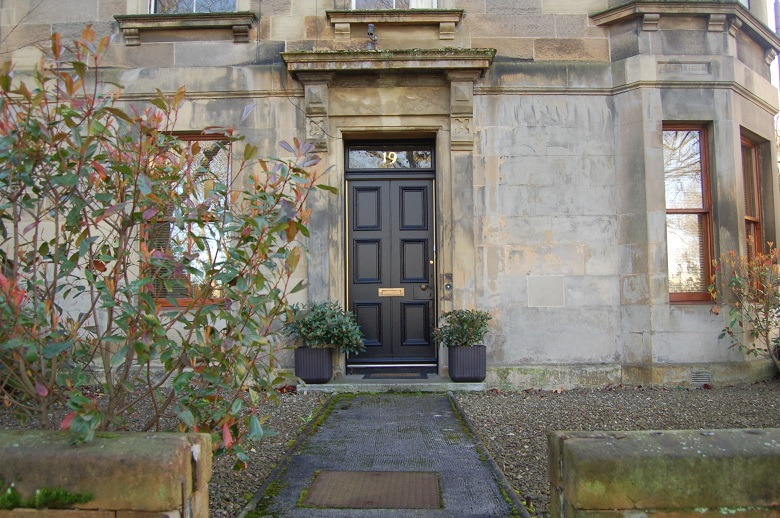 A yellow sandstone tenement with a black front-door flanked by planters