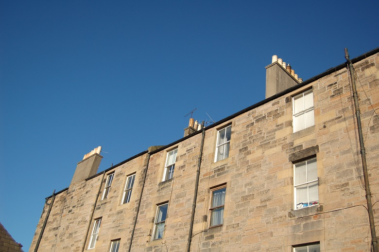 The top two floors of a yellow sandstone tenement with three chimneys