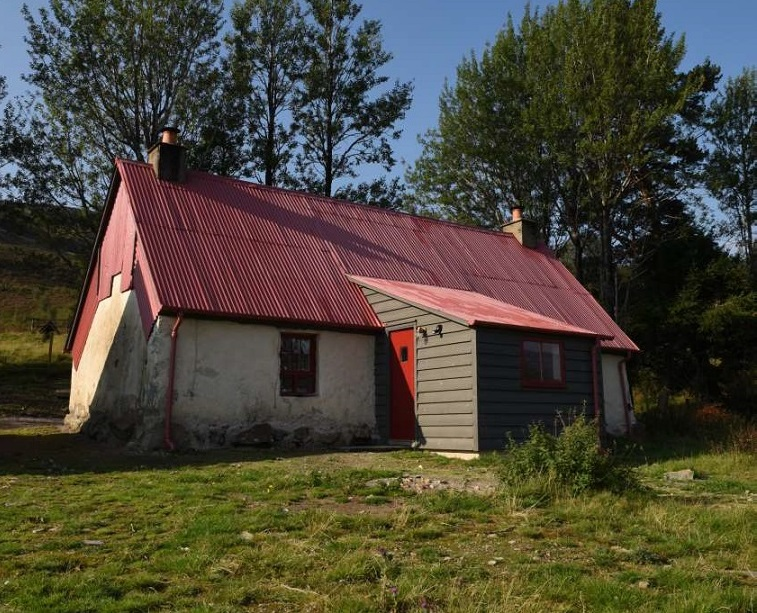 A cottage in the countryside with a corrugated iron work