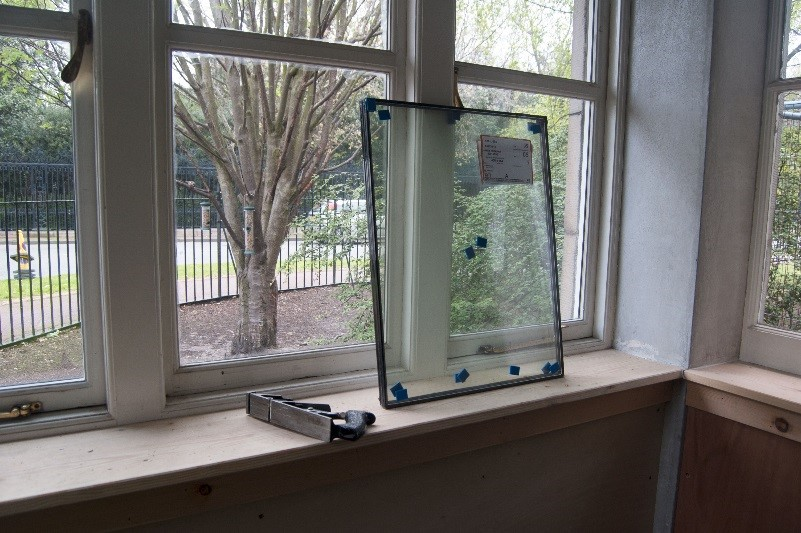 A window, with a small, removed window standing against it on the window sill