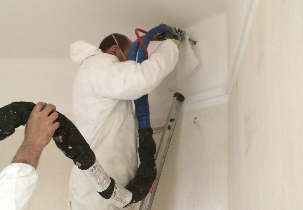 A person on a ladder installing insulation