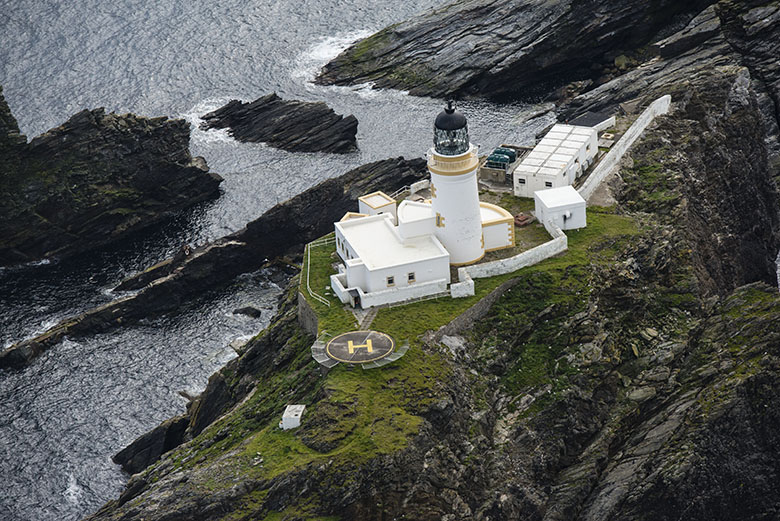 A lighthouse and outbuildings on a small strip of rocky land