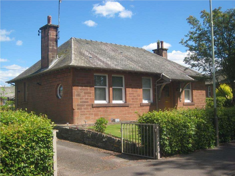 A detached, red sandstone building with a slate roof