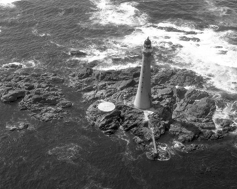 A tall lighthouse on a small area of rock