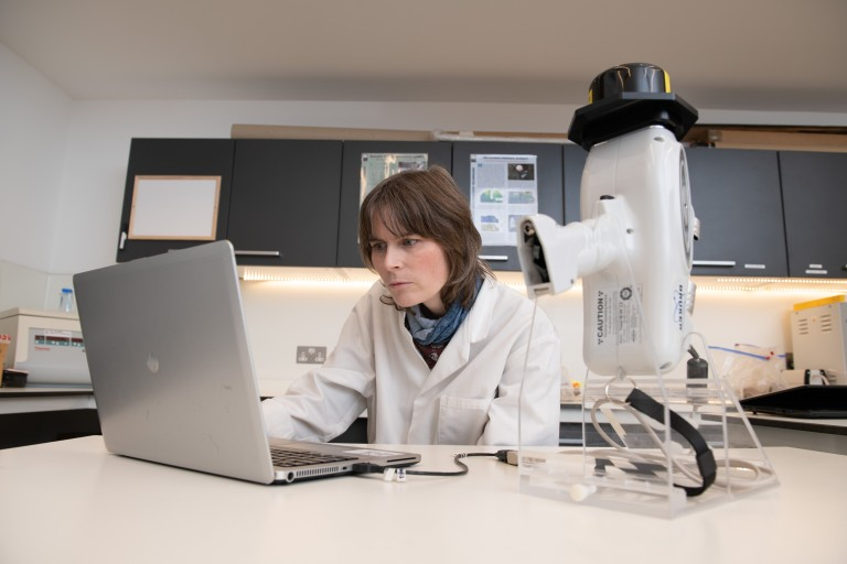 Sarah in a conservation science lab, looking at a laptop screen