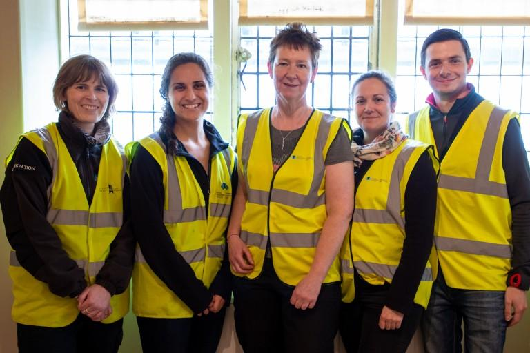 A group of people standing together, wearing high-vis vests