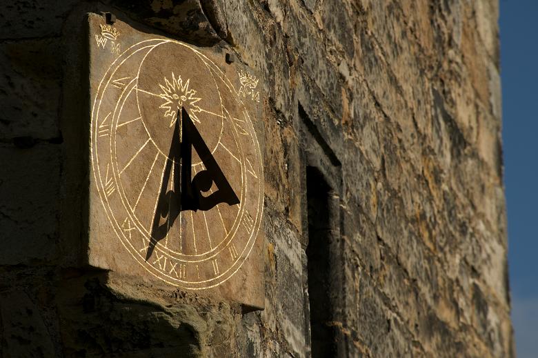 A stone sundial built into a castle wall
