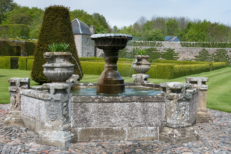 A large iron fountain with stone surround in a historic garden