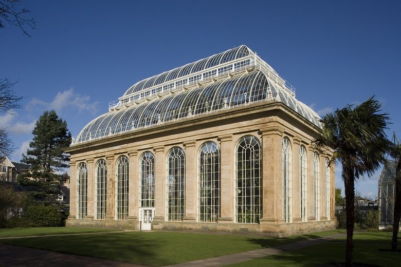 A large, stone and glass glasshouse