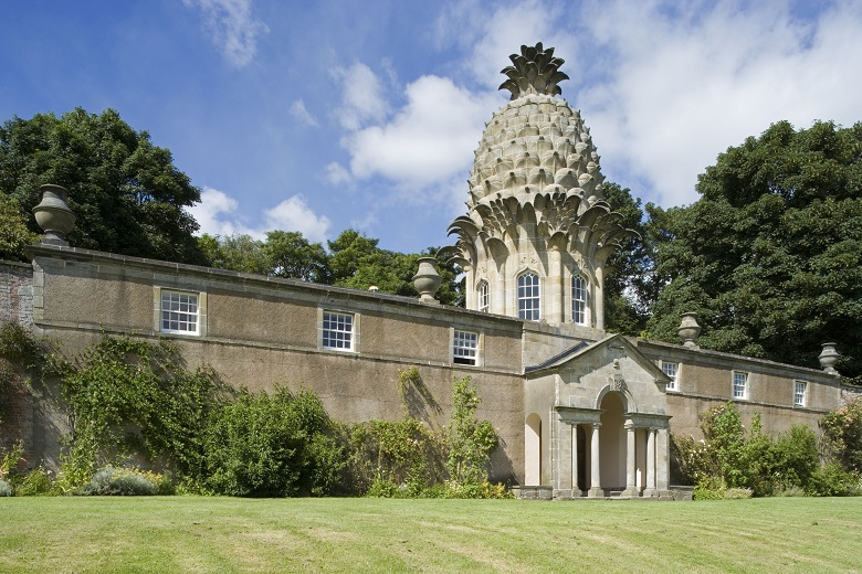 A stone building with a pineapple shaped roof section