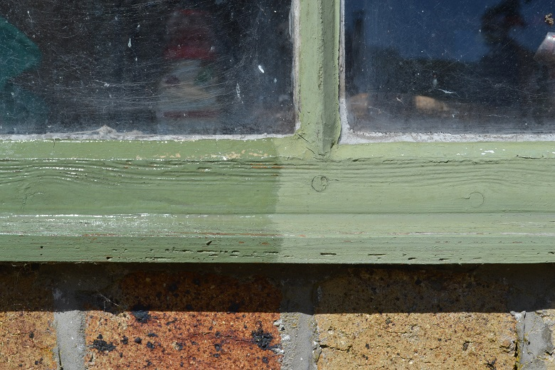 A wooden window frame painted green