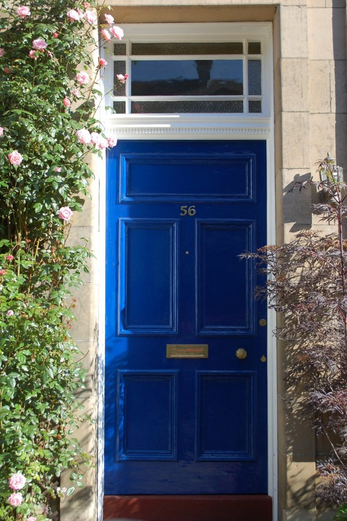 A blue, wooden front door with a small square window above the door