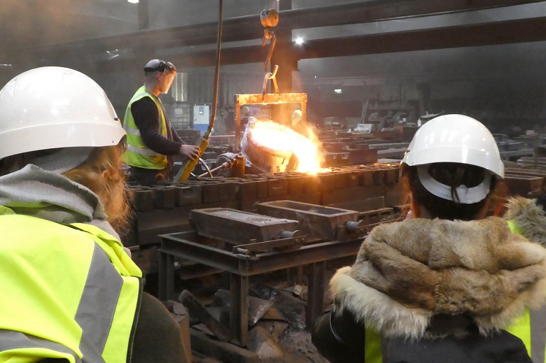 Two people watching someone work in an iron foundry