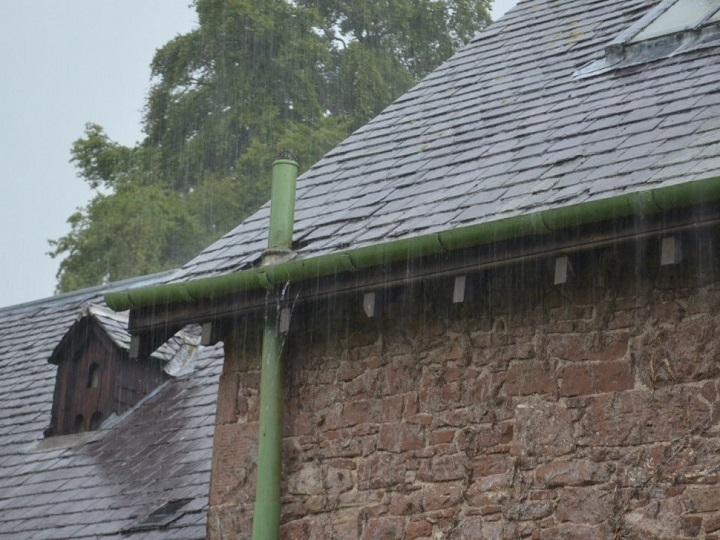 A stone house with a slate roof and iron drainpipe, in the pouring rain