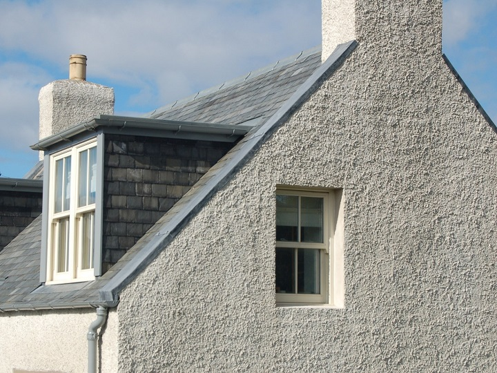 The gable end of a historic house with a slate roof and dormer windows